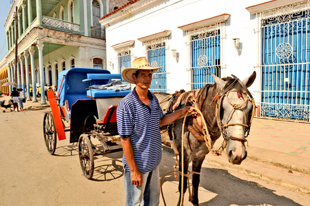REMEIDOS, CUBA, MAY 7, 2009  A man holding a horse that is attached to a carriage, in Remeidos, Cuba, on May 7th, 2009