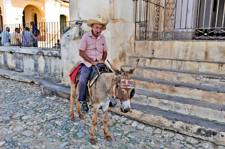 TRINIDAD, CUBA, OCTOBER 27, 2009  An old man sitting on the back of a donkey, in Trinidad, Cuba, on October 27th, 2009