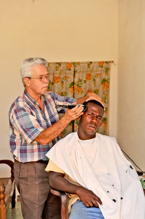 TRINIDAD, CUBA, OCTOBER 27, 2009  A cuban barber barbering a client, in Trinidad, Cuba, on October 27th, 2009