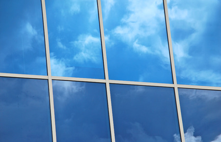 bilding: Merida, Yucatan,Mexico, 2008  Glass windows with white frames reflecting blue sky and white clouds