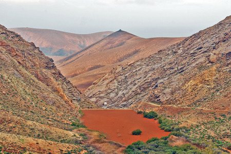 lave: Lanzarote, Canary Islands, Spain  Red lake on a sunny day with a blue sky  Stock Photo