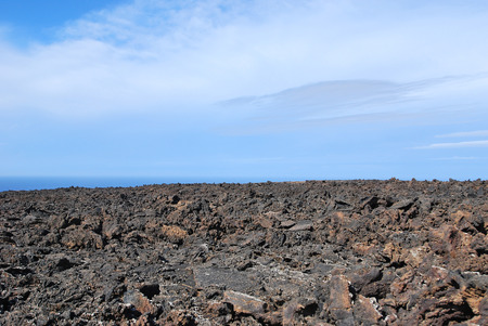 lave: Lanzarote, Canary Islands, Spain  A big lava lake on a sunny day with a blue sky