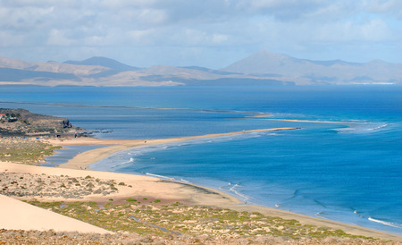 A lagoon beach with foamy wave crests, with mountains and clouds in the horizon and a sand dune in the front, in Fuerteventura, Canary Islands  photo