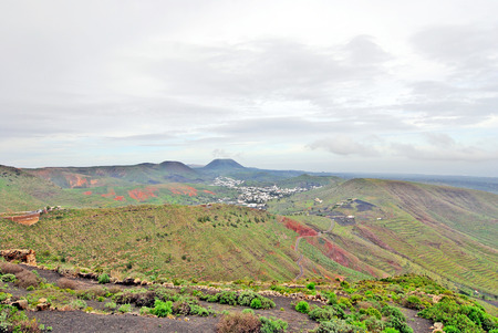 Lanzarote, Canary Islands, Spain  A view from a mountain to a fertile green valley with plantations on the hillsides and small houses on a misty day Stock Photo - 27215870