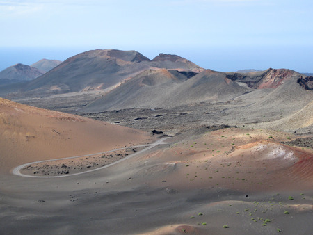 Lanzarote, Canary Islands, Spain  A volcanic mountains landscape with sea far in the horizon, in Timanfaya Natural Park  photo