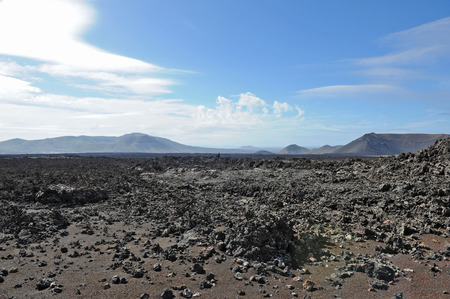 Lanzarote, Canary Islands, Spain  A crater and volcanic mountains in Timanfaya Natural Park, with clouds in the sky  Stock Photo - 27229569