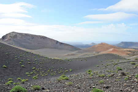 timanfaya natural park: Lanzarote, Canary Islands, Spain  A crater and volcanic mountains in Timanfaya Natural Park, with clouds in the sky