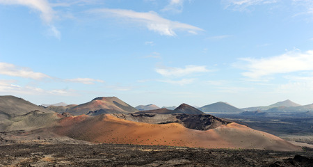 Lanzarote, Canary Islands, Spain  A crater and volcanic mountains in Timanfaya Natural Park, with clouds in the sky  Stock Photo - 27221355