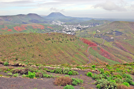 Lanzarote, Canary Islands, Spain  A view from a mountain to a fertile green valley with plantations on the hillsides and small houses on a misty day photo