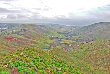 Lanzarote, Canary Islands, Spain  A view from a mountain to a fertile green valley with plantations on the hillsides and small houses on a misty day Stock Photo - 27229684