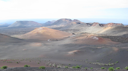 timanfaya natural park: Lanzarote, Canary Islands, Spain  A volcanic mountains landscape with sea far in the horizon, in Timanfaya Natural Park