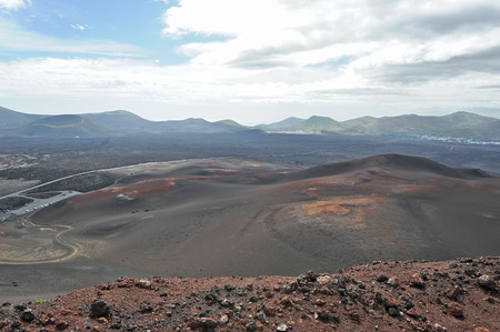 Lanzarote, Canary Islands, Spain  A view from top to bottom into plain of volcanic mountains, a road,  and sea far in the horizon, in Timanfaya Natural Park  Stock Photo - 27227592
