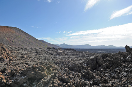 lave: Lanzarote, Canary Islands, Spain  A lava field with mountains in the horizon, in Timanfaya Natural Park