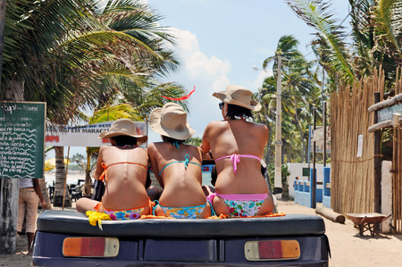 Maracaipe Beach, Pernambuco, Brazil, 2007  Three women with different heights wearing bikinis and hats, sitting on a buggy