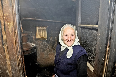 OHRID, MACEDONIA, MAY 17, 2011  And old Macedonian lady making home made alcohol in the countryside of Ohrid, Macedonia, on May 17th, 2011