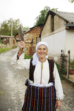 OHRID, MACEDONIA, MAY 17, 2011  An old Macedonian lady posing in a national suit with a butchers knife in her hand, in the countryside of Ohrid, Macedonia, on May 17th, 2011