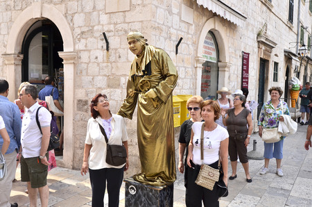 DUBROVNIK, CROATIA, MAY 22, 2011. Two middle aged tourist women posing with a golden living statue in the old town of Dubrovnik, Croatia, on May 22nd, 2011.