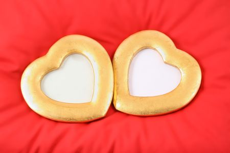 two gold hearts are situated on red pillow Stock Photo - 2337506