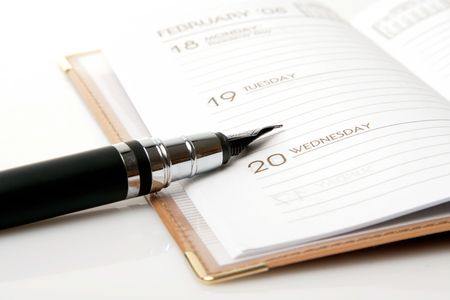 appointment book: ink pen and brown calendar over white background Stock Photo