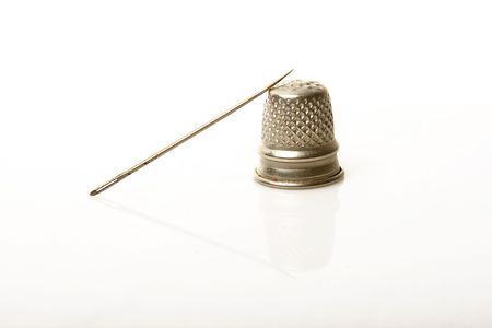 crewel: silver thimble and needle over white background