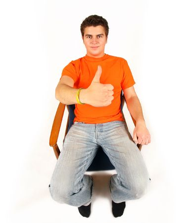 young man in orange t-shirt sitting and showing OK photo