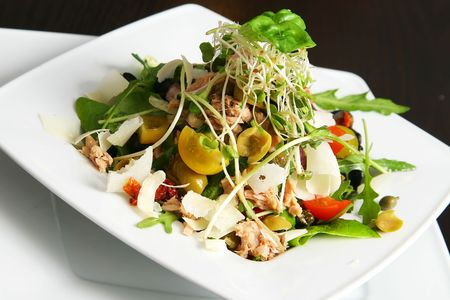 salad with tuna on the plate over table photo