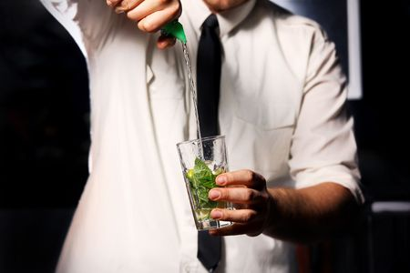 barman making drink with mint and ice photo