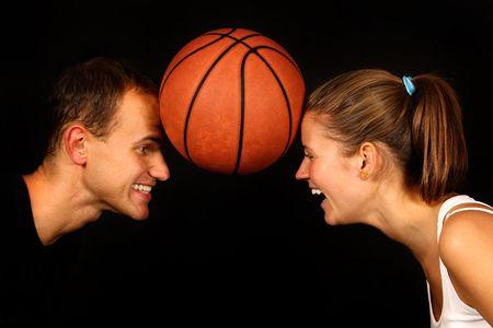 young couple over black with basketball ball Stock Photo - 6786237