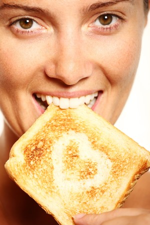 Young girl is eating fresh toast with heart shape on it photo