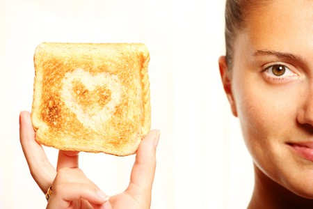 Young girl is holding toasted bread with heart shape on it photo