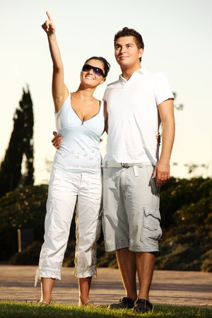 A young nice couple on a walk in the park. The girl is pointing at something and smiling. photo