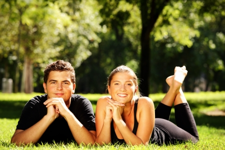 A young nice couple resting in the park and smiling over natural background