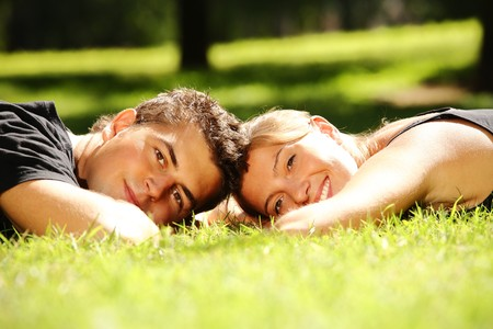Young couple lying in the park and smiling Stock Photo - 7890341