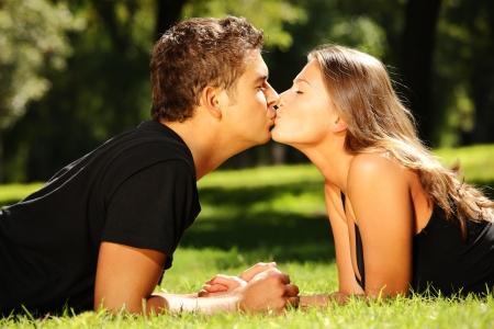 enamorados besandose: Una joven pareja cute tumbado en la hierba en el parque y besar  Foto de archivo