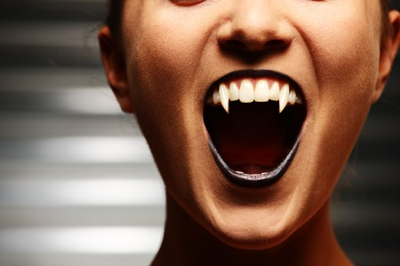 fangs: Close up of a vampire womans mouth over dark background