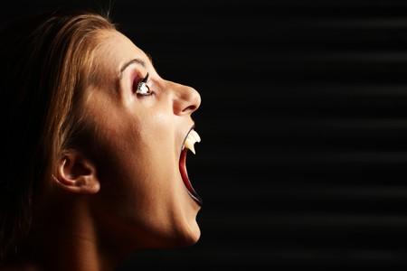 vampire teeth: A vampire woman screaming over black background Stock Photo