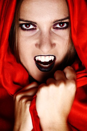 Woman vampire showing her fang and covered in red