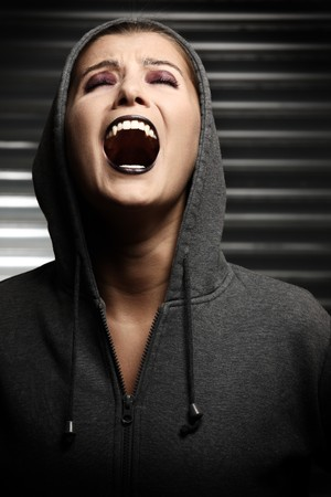 devil girl: A screaming hooded vampire over dark background