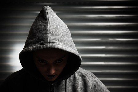 A hooded vampire woman over dark background photo