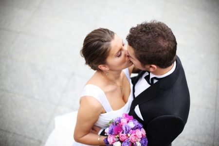 Beautiful picture of a nice young married couple kissing on a street photo