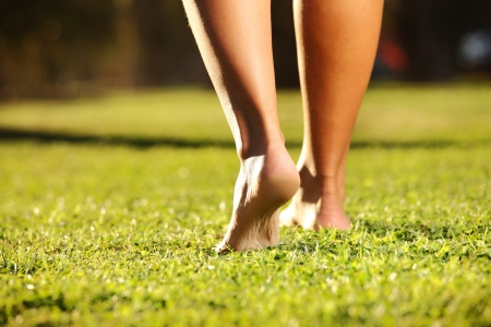 barefeet: A picture of female legs on a grass on a sunny summer or spring day Stock Photo