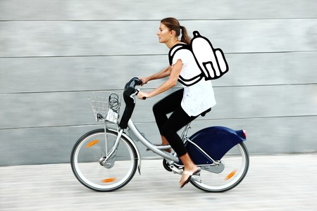 Young pretty woman going to school by bike being in a hurry over grey background photo