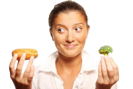 decission: Un ritratto di giovane donna con ciambella e brocoli e cercando di decidere cosa mangiare Archivio Fotografico