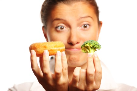 decission: A picture of a young woman trying to decide between healthy and unhealthy food Stock Photo