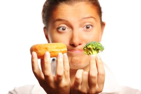 decission: Un ritratto di una giovane donna, cercando di decidere tra cibo sano e malsano