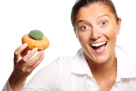 decission: A picture of a young woman finding perfect compromise between eating a donut and broccoli