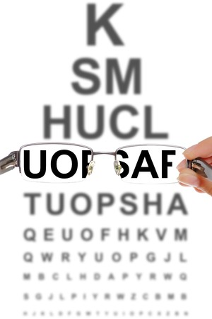 optician: A picture presenting a pair of glasses over a board with letters at optitians Stock Photo
