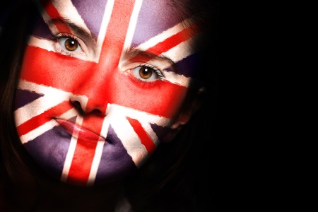 A close up of a british flag on a female face over dark background Stock Photo