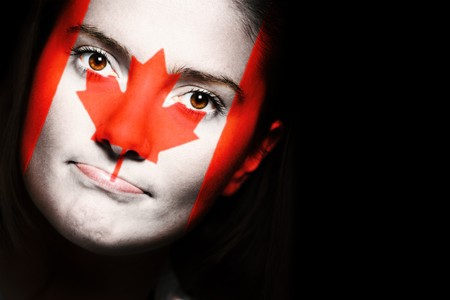 A close up of a canadian flag on a female face over dark background photo