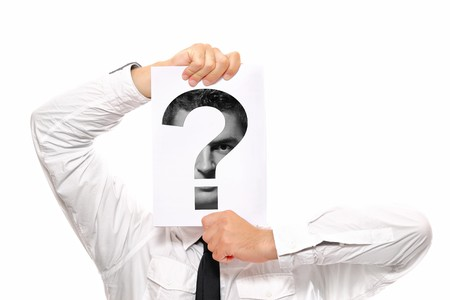 Businessman holding a piece of paper over his face with a question mark on it